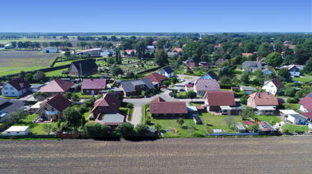 Aerial view of a new housing estate with detached houses and gardens. At the edge of a village with a field in the foreground, near a cemetery, made with drone