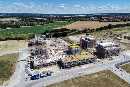 Large construction site on the outskirts behind a village with meadows and fields in front, aerial view, made with drone