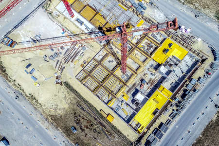 Aerial view from a greater height above the cranes of a construction site with the carcasses for new apartments in a growing German city, made with drone