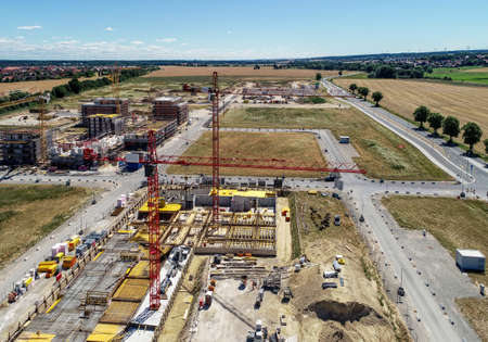 Construction site with cranes and the shells for new houses, in the background preparation of the area for parking the cars, aerial photo, made with drone Banco de Imagens