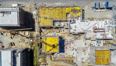 Vertical view from a great height of a square building shell covered with yellow sealing mats, aerial photo, nadir, made with drone
