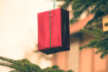 Gift wrapped in red glossy foil hung on a fir tree as a decorative element for the Christmas season, holiday Banco de Imagens