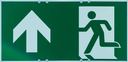 Sign with the pictogram of a walking person and an arrow in white on a green background, indication of an escape route in case of danger, abstract