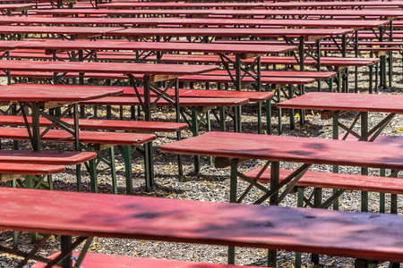 Ugly old red wooden benches and tables, from which the paint peels off, in a beer garden in Hannover Banco de Imagens