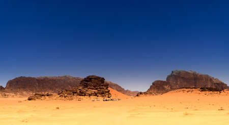 View to a camp for tourists in the desert of the nature reserve of Wadi Rum, Jordan, dark blue sky above red desert