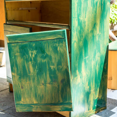Old broken cabinet, which is prepared with a first coat of green paint for further repair and renovation, do it yourself