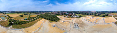 Panorama in high resolution, composed of photos with the drone, with a view of a new development with several streets and dead ends, old village in the background, aerial view
