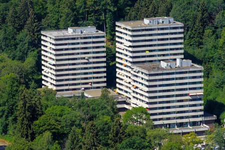 Ugly old blocks of flats with holiday apartments for tourists at the edge of the Harz mountains in the middle of the forest. Banco de Imagens