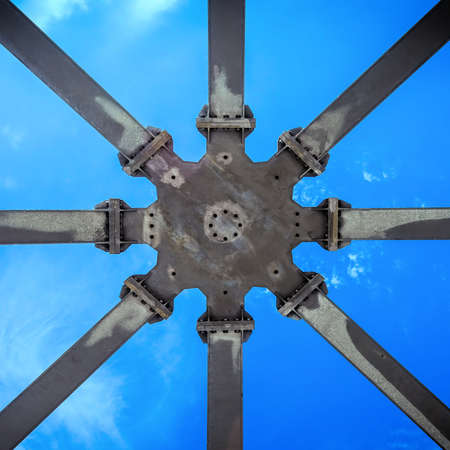 Star-shaped supporting structure taken from below against the blue sky, abstract geometric impression.