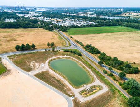 Aerial view of a rain retention basin at the edge of a new development, taken oblique. Archivio Fotografico