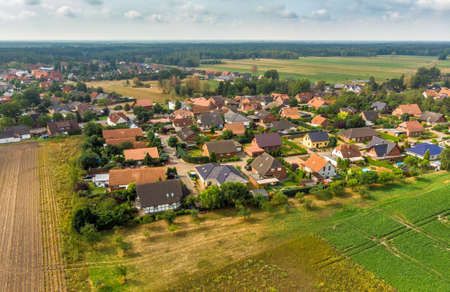 Aerial view of a small village in northern Germany with large arable land at the edge of the village.