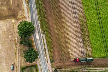 Abstract vertical aerial view of a narrow country road at the edge of an area of arable land with different colored stripes.