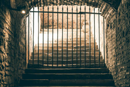 A frightening stairway leading to a passage blocked by an iron grid in a medieval dungeon 스톡 콘텐츠