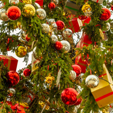 Magnificent Christmas tree decorated with silver and red balls and packages wrapped in wrapping paper, close-up view