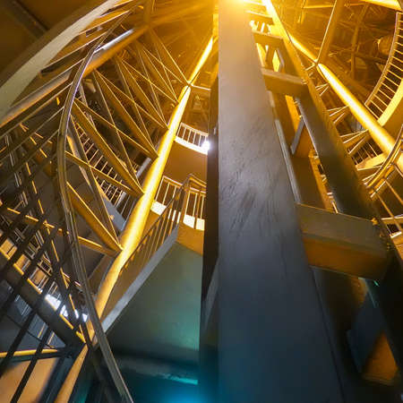 Night-time recording of the illuminated spiral staircase leading from the platform of an underground to the outside of the building.