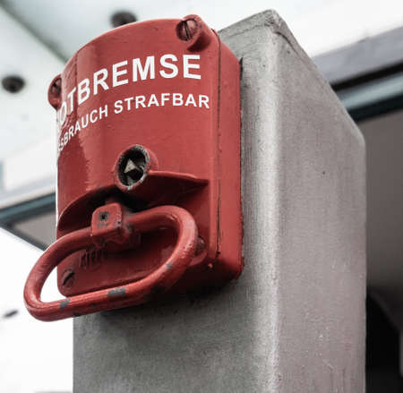 Red emergency brake to stop a large rolling staircase, with German inscription