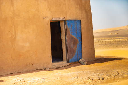Abstract unreal picture of the corner of a house in the desert with an open blue damaged door of iron