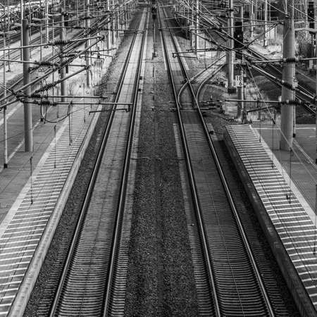 Perspective view of railway tracks with overhead lines next to a platform, monochrome