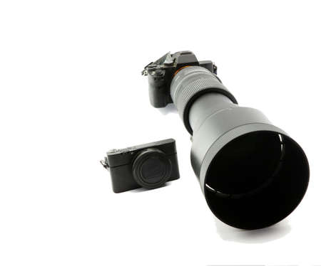 Mirrorless blac system camera with ultratele telezoom 150mm to 600mm and tiny compact camera in comparison