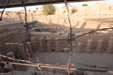 Unclearly depicted columns of an excavated temple near Kerma in Sudan behind sharply focused barbed wire