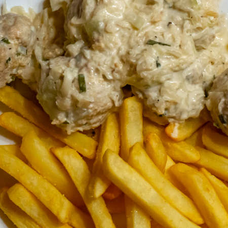 Polish meatballs in cream sauce with celery and spring onions on french fries made from fresh potatoes, homemade fare, food