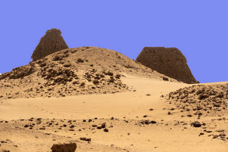 A pyramid destroyed beyond recognition in the foreground, two restored pyramids in the background in the desert of Sudan, Africa Foto de archivo