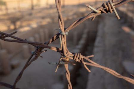 Rusty barbed wire to protect an excavation site in the desert of Sudan, Africa 版權商用圖片