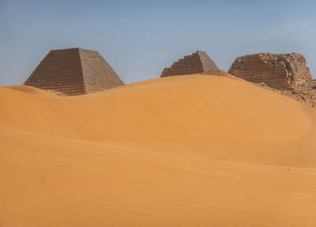 Pyramids behind a large sand dune in the desert of Sudan, Africa 版權商用圖片