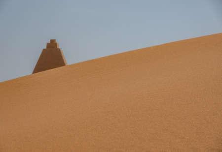 Tip of a pyramid behind a dune in Sudan 版權商用圖片