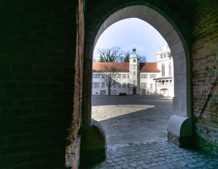 Castle viewed from afar through the passage behind the moat of the castle