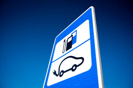 recharge: Road sign of electric car battery recharge station over deep blue sky background