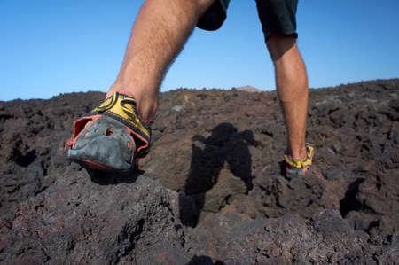 Close-up of man s feet walking on lava field in sport shoes  Canary Islands, Lanzarote, Timanfaya National Park  Stock Photo