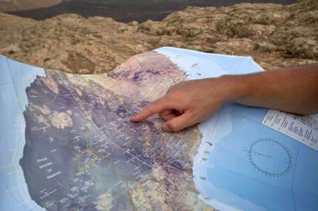 Male backpacker looking for a route on the tourist map/orthophoto map on the Calder Blanca, Timanfaya National Park, Lanzarote, Canary Islands, Spain. Stock Photo - 16439039