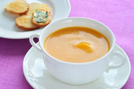 Soup made of roasted-pumpkin, parsnip, potatoes, stock and wine in a white bowl.