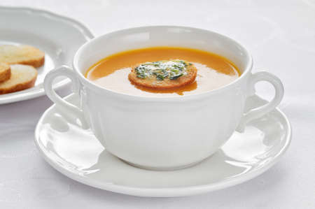 Soup made of roasted-pumpkin, parsnip, potatoes, stock and wine in a white bowl. photo