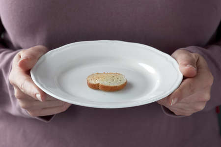 calories poor: One small toast on the white plate. Small portion of food. Conceptual photo.