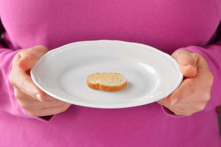 One small toast on the white plate. Small portion of food. Conceptual photo.