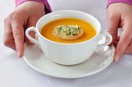 Serving homemade roasted-pumpkin soup in white bowl on white tablecloth. Stock Photo - 17345375