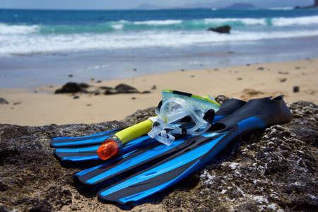 Schnorchelausrüstung (blau Flossen, Schnorchel und gelb transparent Tauchermaske) auf dem Felsen am Strand. Kanarische Inseln, Lanzarote, Papagayo Beach. Standard-Bild - 17815249