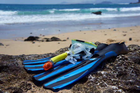 Snorkeling Equipment (blue flippers, yellow snorkel and transparent diving mask) on the rock beach. Canary Islands, Lanzarote, Papagayo Beach.