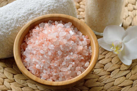 Pink salt from the Himalaya. Closeup of pink SPA salt in wooden bowl with orchid flower and towel. Stock Photo