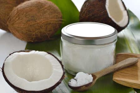 aceite de coco: Los cocos y aceite de coco org�nico en un tarro de cristal en el tratamiento del pelo blanco de fondo