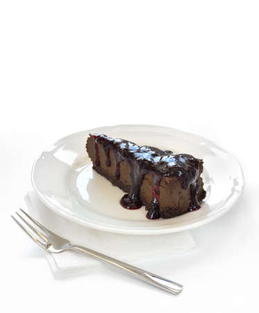 Slice of chocolate cheesecake with blackcurrant jam on white plate. Cheesecake made of cheese, cream, dark chocolate and some espresso and amaretto. Crust made of almond, biscuits and chocolate. Stock Photo - 18940971