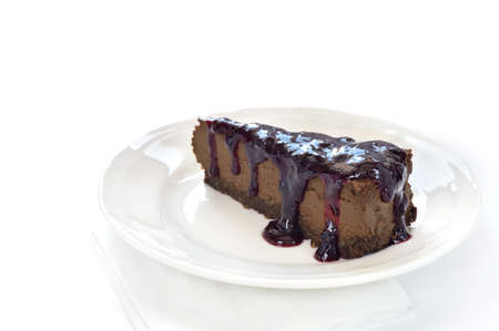 Slice of chocolate cheesecake with blackcurrant jam on white plate. Cheesecake made of cheese, cream, dark chocolate and some espresso and amaretto. Crust made of almond, biscuits and chocolate. Stock Photo - 18940977