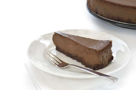 amaretto: Slice of chocolate cheesecake on white plate. Cheesecake made of cheese, cream, dark chocolate and some espresso and amaretto. Crust made of almond and biscuits. Stock Photo