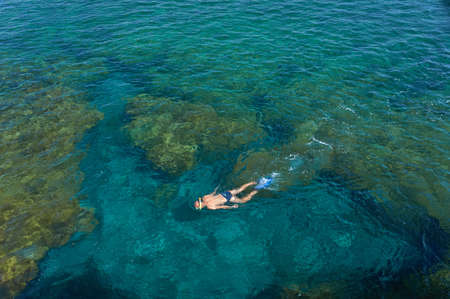 canary island: Young man snorkeling in transparent shallow ocean