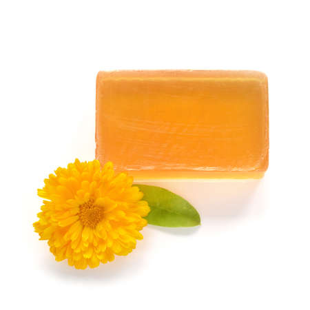 glycerin soap: Orange handmade glycerin soap and marigold flower on white background  Hypoallergenic soap with marigold extract  Beauty care  Stock Photo