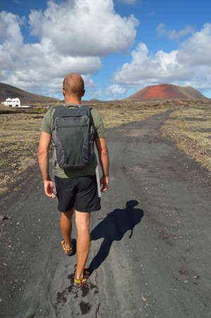 rough road: Alone hiker on a volcanic path  Canary Islands, Lanzarote, Montana del Fuego  Stock Photo