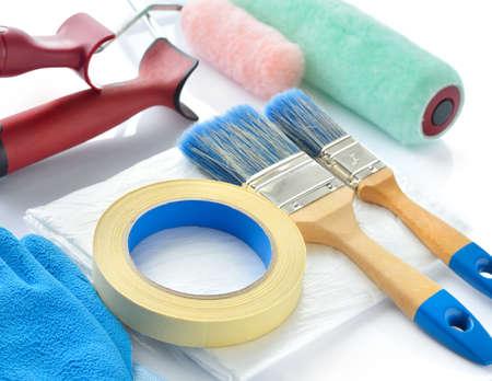 ペイントの白い背景の上のツール ペイント ローラー、ブラシ、ドロップ布、マスキング テープ、手袋 写真素材