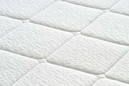 quilted: Close-up of white mattress texture  Patter of quilted material  Comfortable mattress  Copy space  Stock Photo